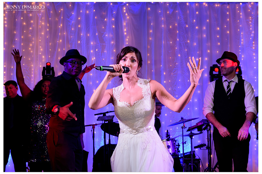 The bride gets on stage with the band with a microphone to dance and sing to her guests.