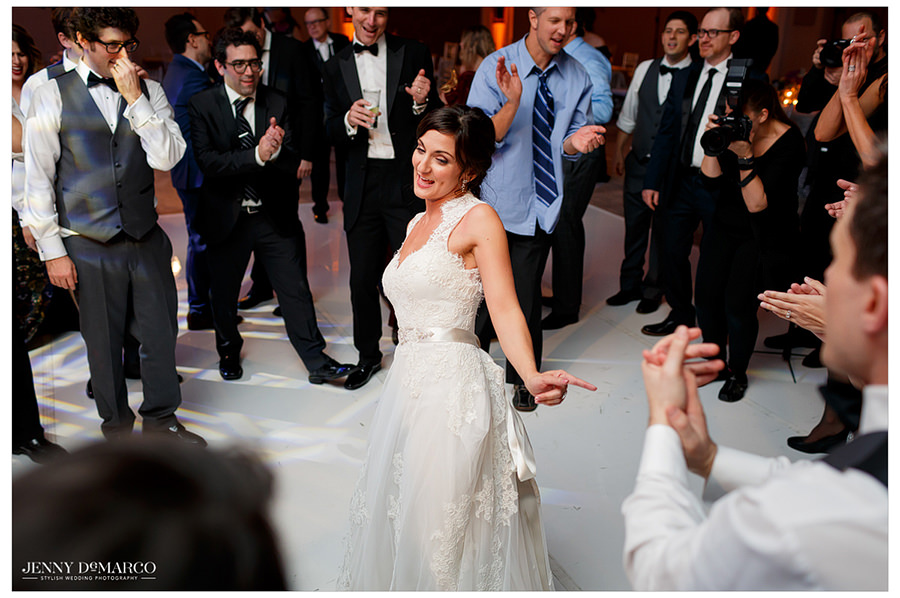 The bride dances in the center of the ballroom floor as guests gather around her to dance and clap.