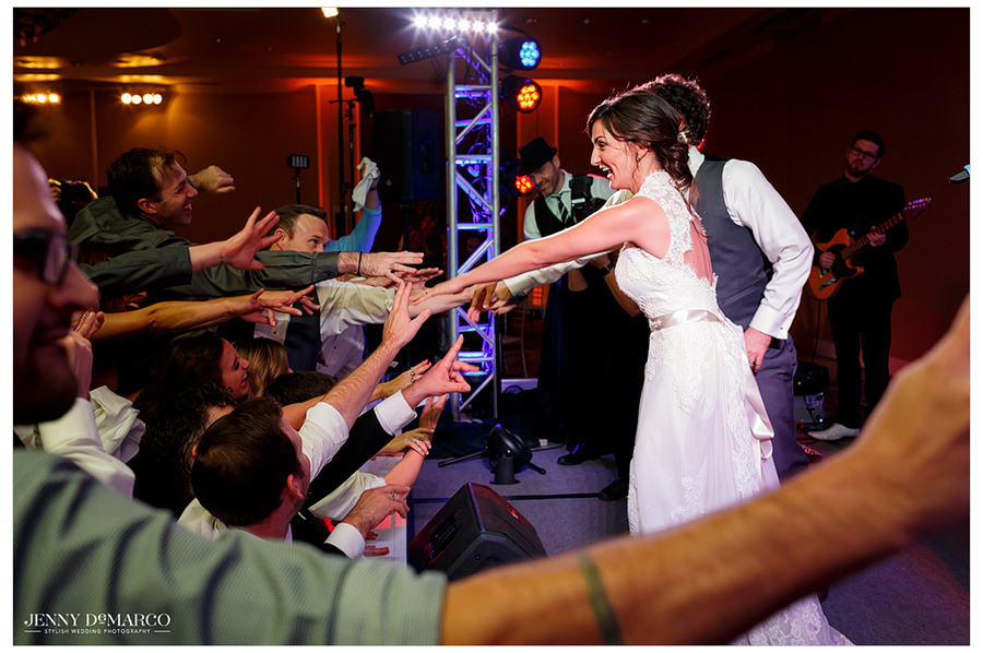 The bride and groom reach out from stage to their guests.