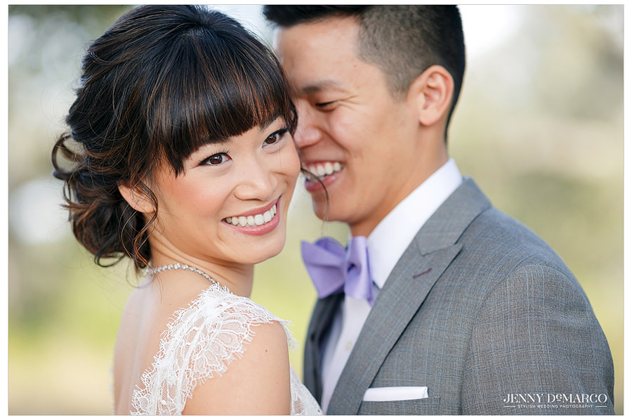 A close up shot of the bride and groom laughing and smiling together on their wedding day.