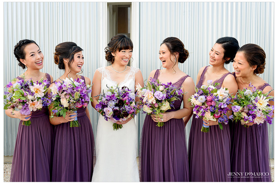 The bride surrounded by her five bridesmaids in beautiful purple gowns with flowers to match.