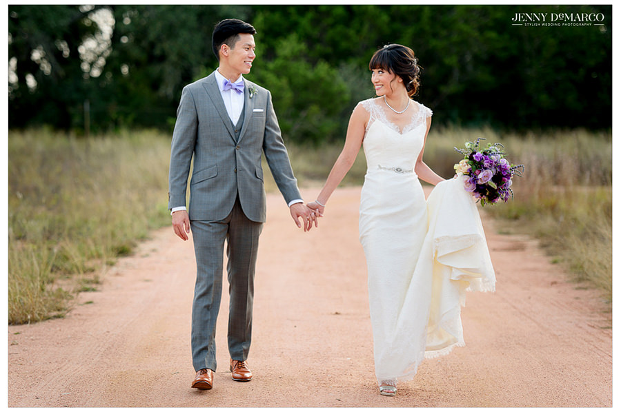 The bride and groom walk together holding hands down a gravel road in a beautiful field.