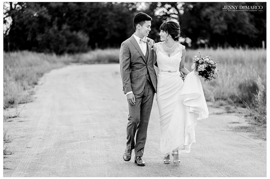 A black and white shot of the bride and groom walking together and talking before their wedding.