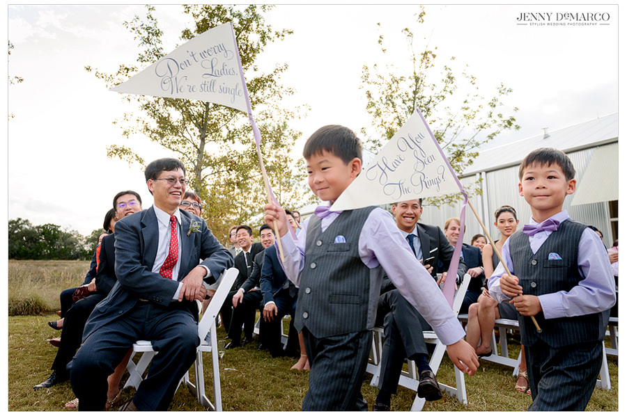 Children walk down the aisle with signs in preparation of the bride and grooms arrival.