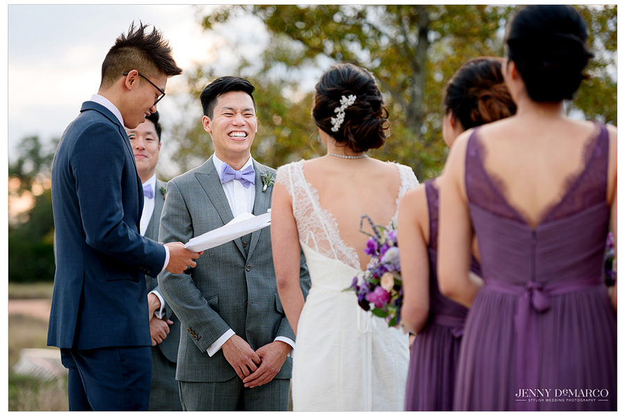 The groom smiles with joy and laughter during the ceremony.