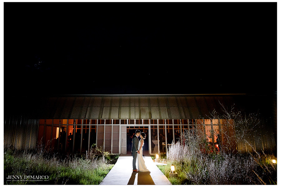A beautiful landscape night shot of the bride and groom holding hands and having a moment outside their reception at Prospect House.
