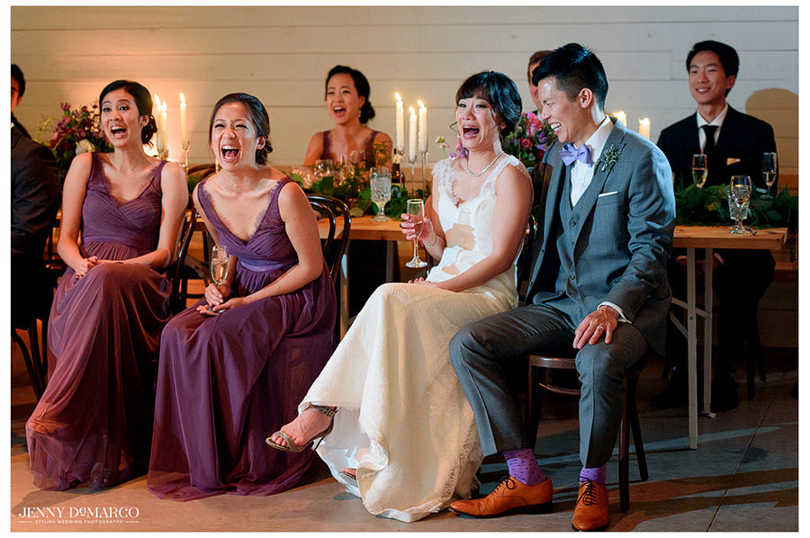 The bride, groom, and bridesmaids laugh as guests give their toasts.