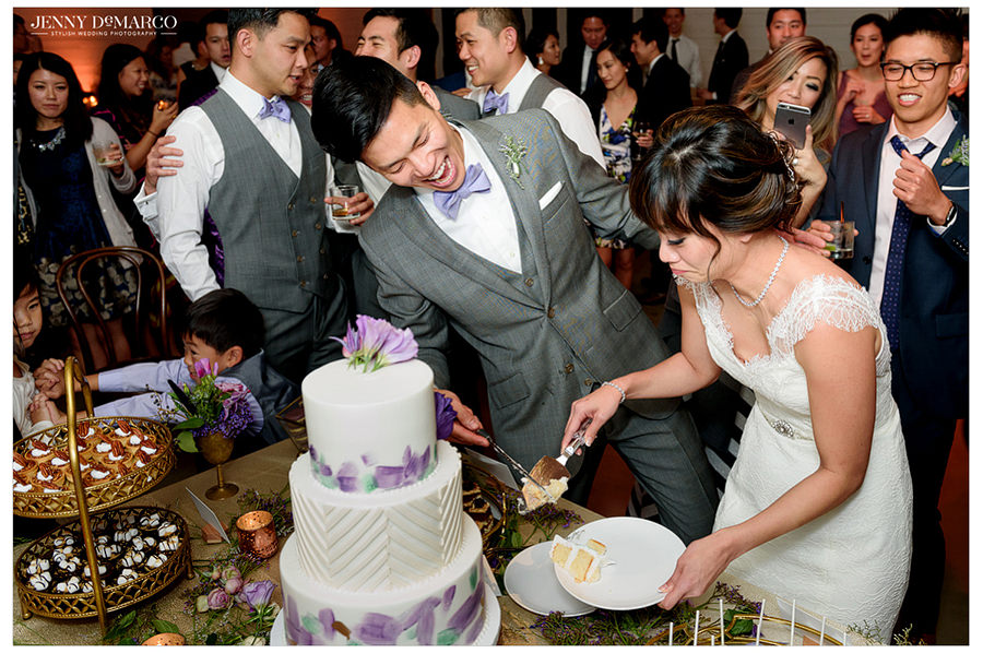 The bride and groom cut the cake and laugh as guests gather to watch.
