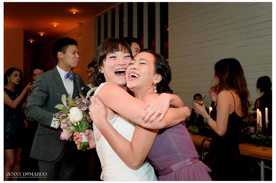 The bride holds and hugs one of her bridesmaids as they laugh together.