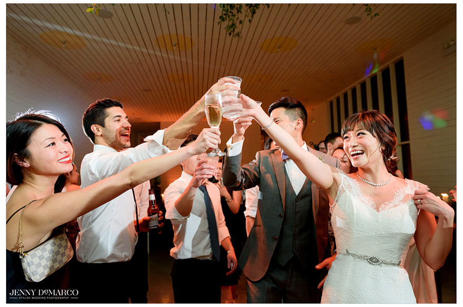 The bride and guests lift up their drinks for a toast.