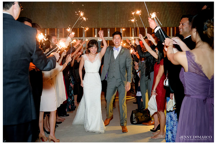The bride and groom exit the reception as guests gather with lighted sparklers to send them off.