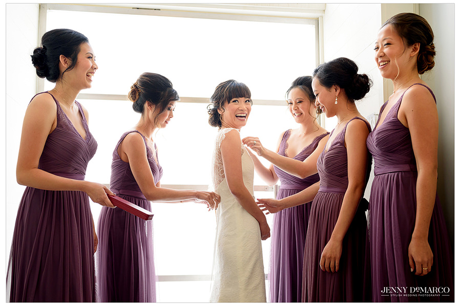 Bridesmaids gather around the bride to see her in her gown and help with final touches.