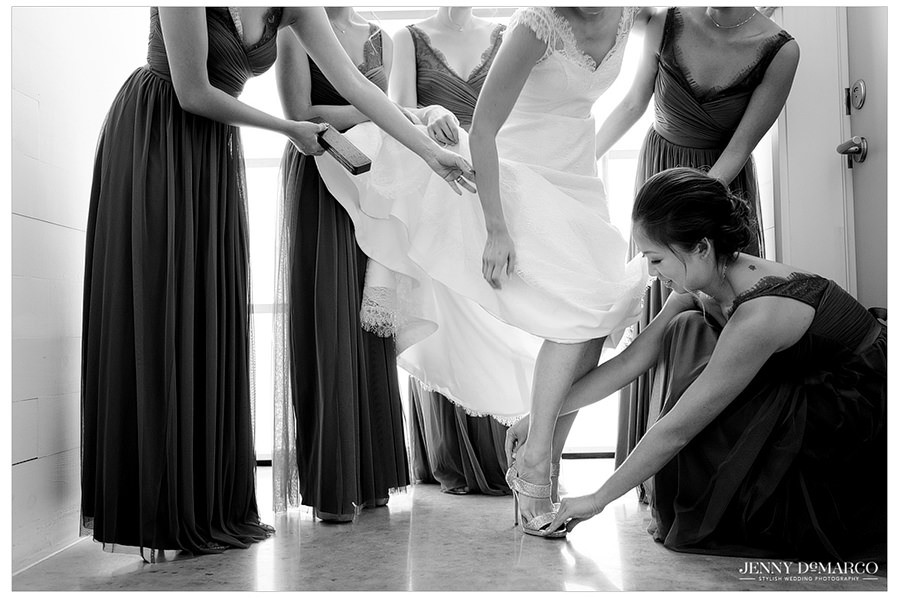 The bridesmaids hold up the wedding dress and help the bride put on her wedding day shoes.