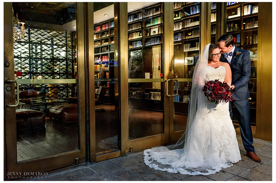 Bride and groom cuddled outside the gold doors of cafe medici in downtown Austin.