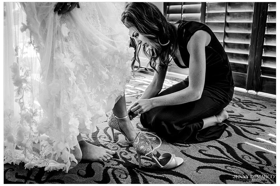 A bridesmaid helping the bride into her shoes before the first look.