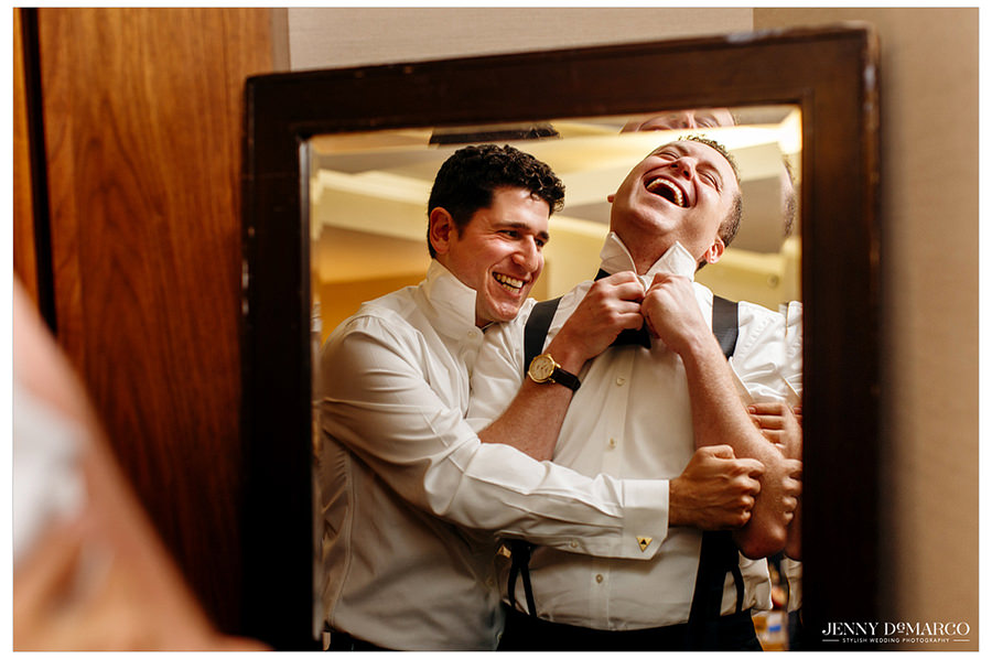 Candid shot of the groomsmen and groom getting ready and laughing before going to see the bride for the first look.