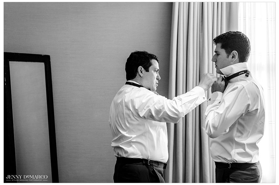 Groomsmen helping each other get ready and tie their bowties before the wedding.