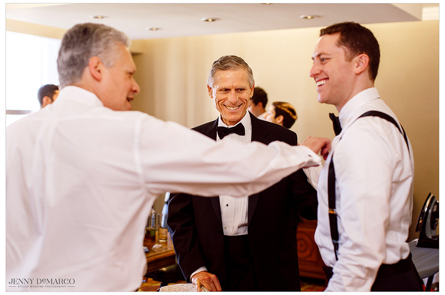 Groom talking and laughing with his father and grandfather on his wedding day.