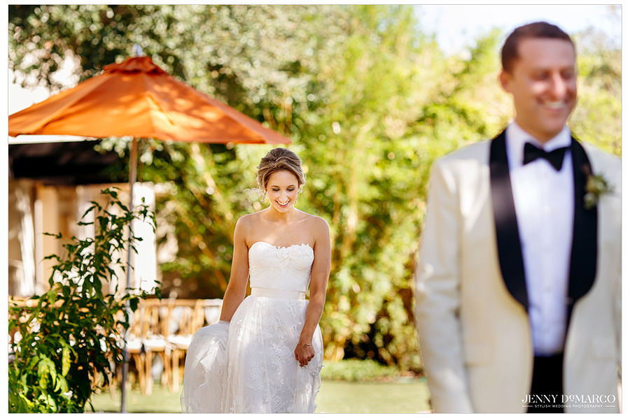The bride walking up for the big first look. The groom wits smiling at the thought of her.