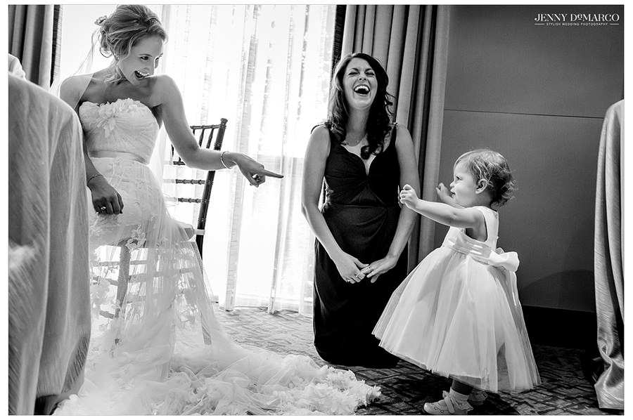 The bride laughing and having fun with the flower girl.