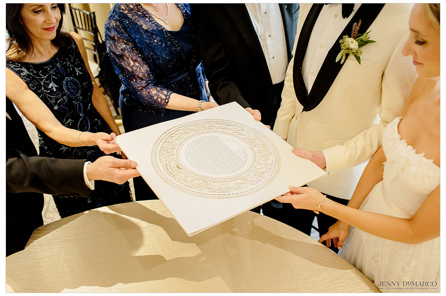 The parents passing the Ketubah to their children to sign.