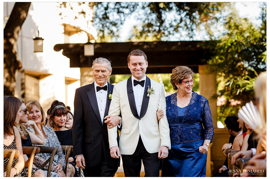 The groom being escorted down the aisle by his parents.