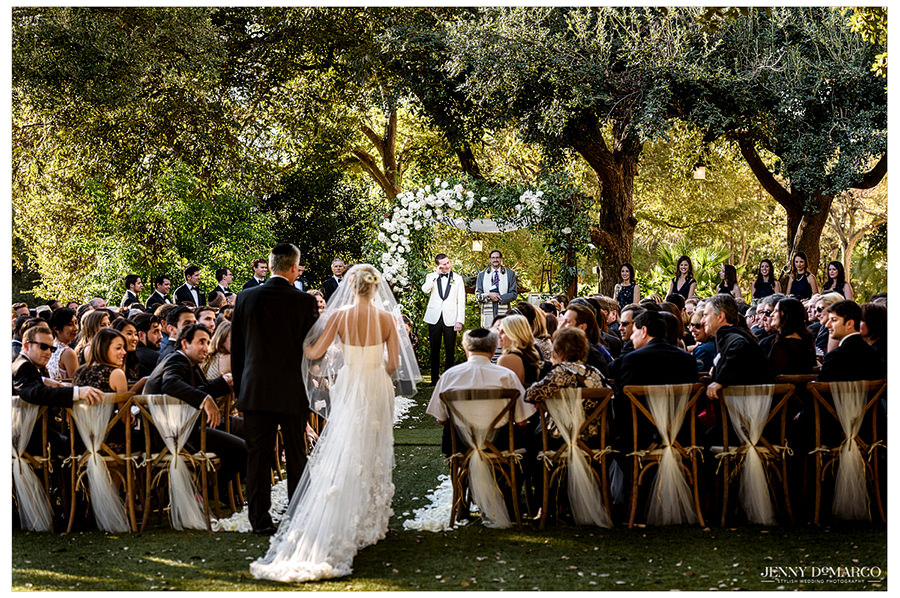 Bride walking down the aisle with her father to give her away on The Four Seasons lawn.
