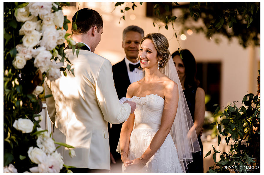 The bride smiling as the groom reads her his vows.