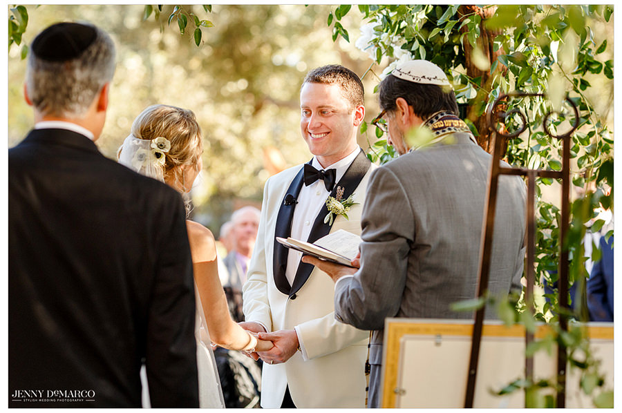 The groom smiling at the bride as the Rabbi talks.