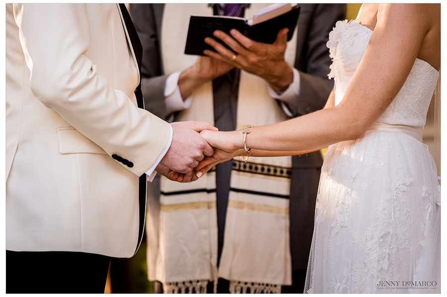Detail shot of the bride and groom holding hands during the ceremony.