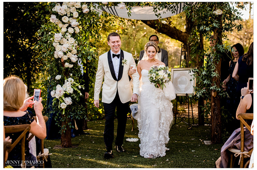The bride and groom walking up the aisle as a married couple for the first time.