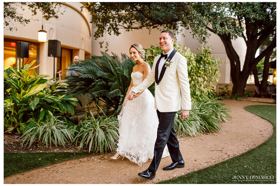 The happy newlyweds walking together to the reception.