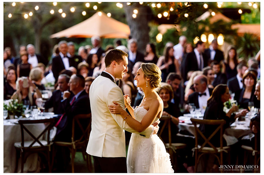 The bride and groom during their first dance under the festoon lights on the Four Seasons lawn.