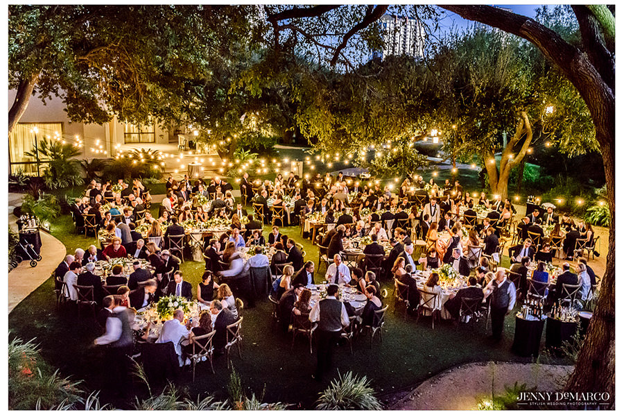 An overhead shot of the reception party outside at the Four Seasons Hotel under the festoon lights.