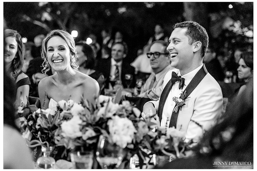 The bride and groom laughing at a toast during the reception.