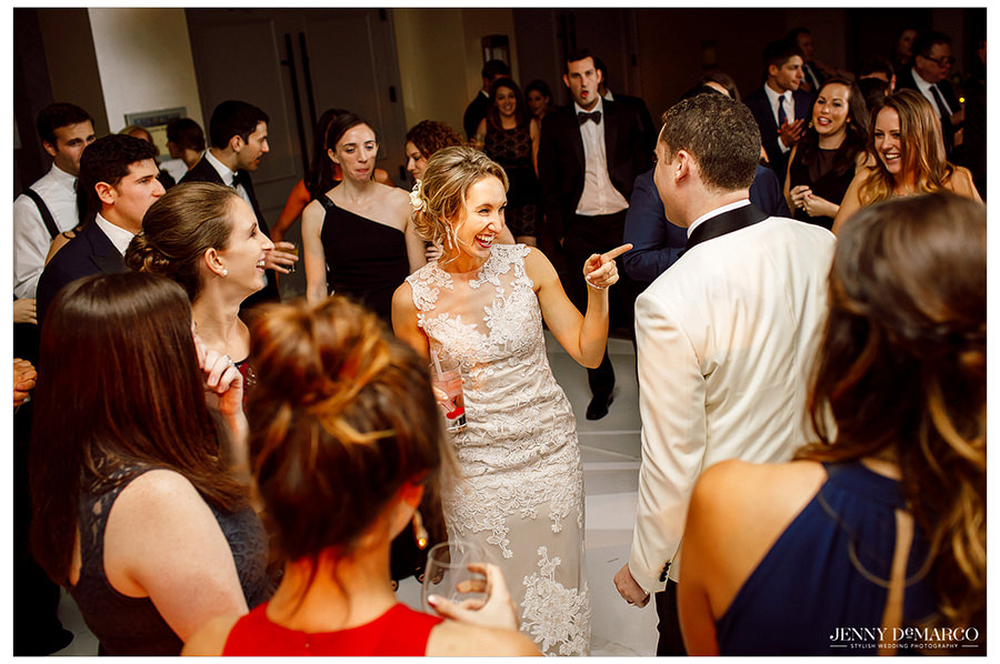 The bride laughing with her friends and the groom at the reception.