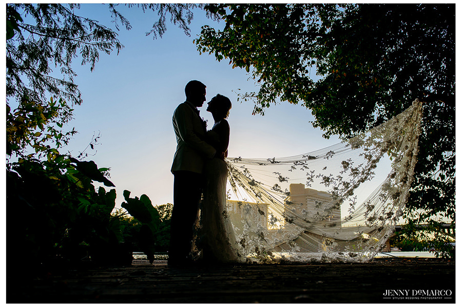 Beautiful portrait of the bride and groom as the sunsets with her veil all spread out outside.