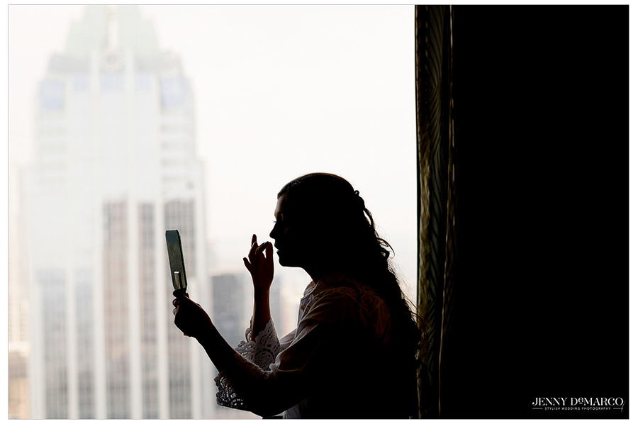 Silhouette of bring putting her makeup on with Frost Bank Tower in the background.