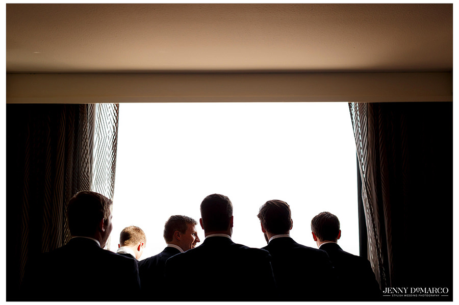 Groomsmen looking out the window preparing to walk down the aisle.