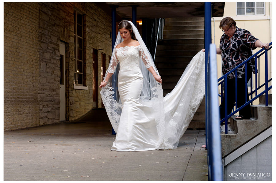 Bride walking down aisle with veil spread out.