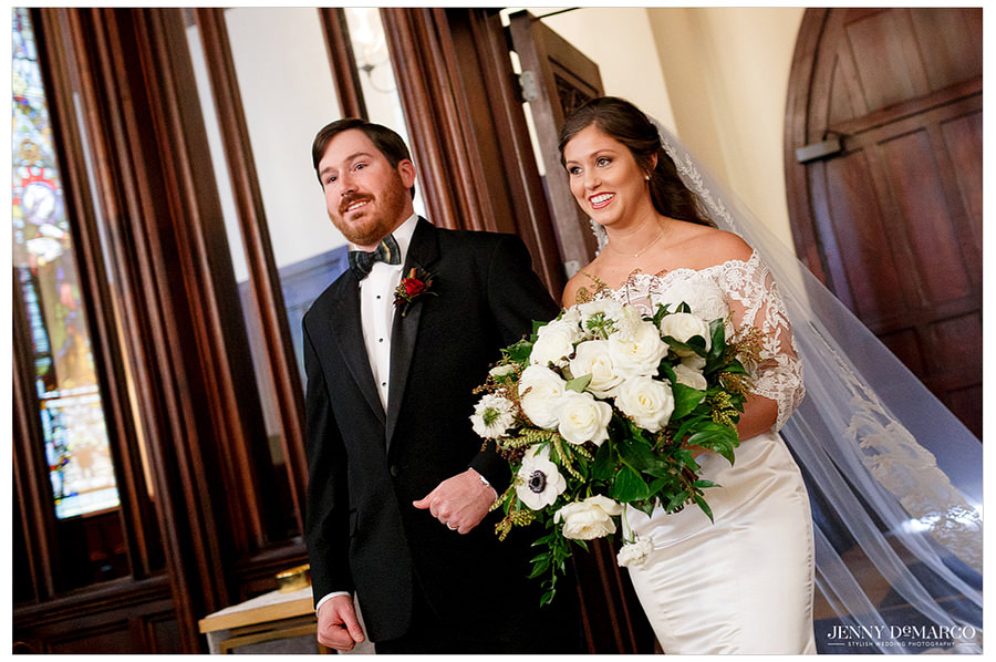 Bride walking with dad down the aisle with big bouquet of flowers.
