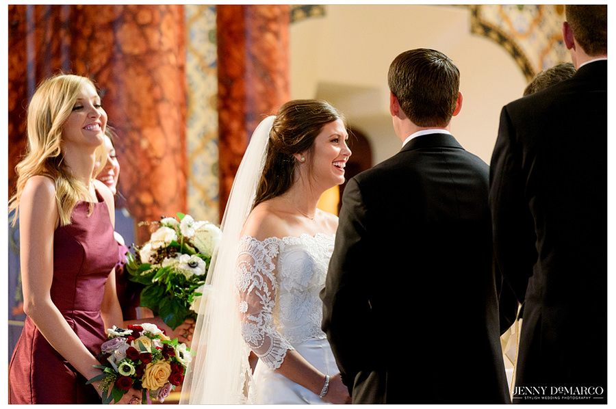 Bride laughing during vows at catholic church.