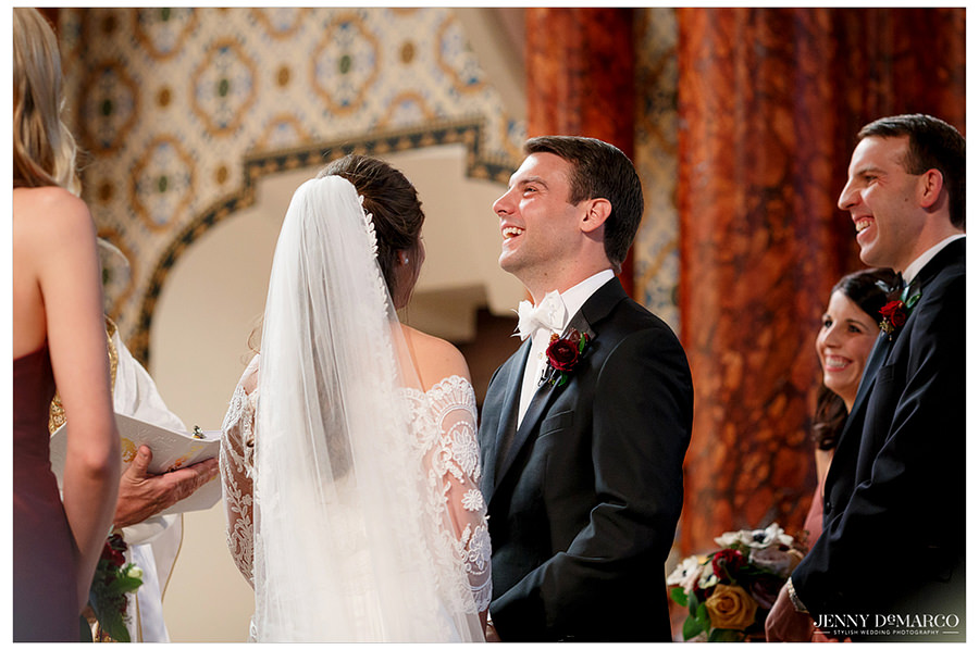 Groom laughing during vows at catholic church wedding.