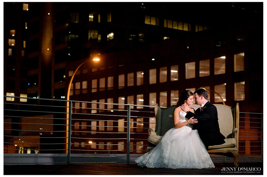 Bride and groom portrait sitting on bench on rooftop at Brazos Hall.