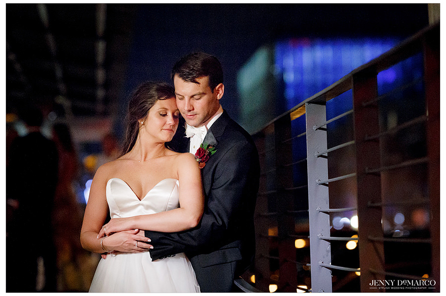 Portrait of bride and groom with city skyline at night behind them.