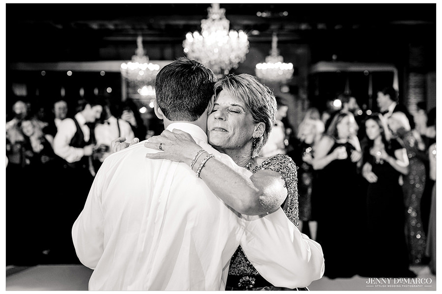 Mother son dance while mom smiles happily.