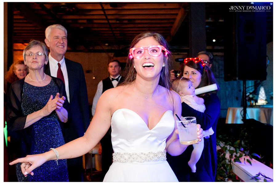 Bride with light up glasses on during reception.