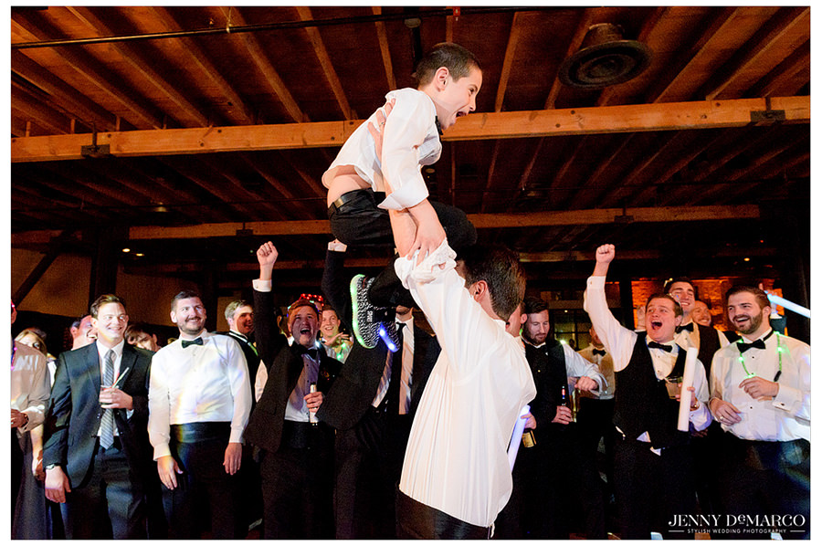 Groom lifted the ring bearer in the air proud that he caught the garter.