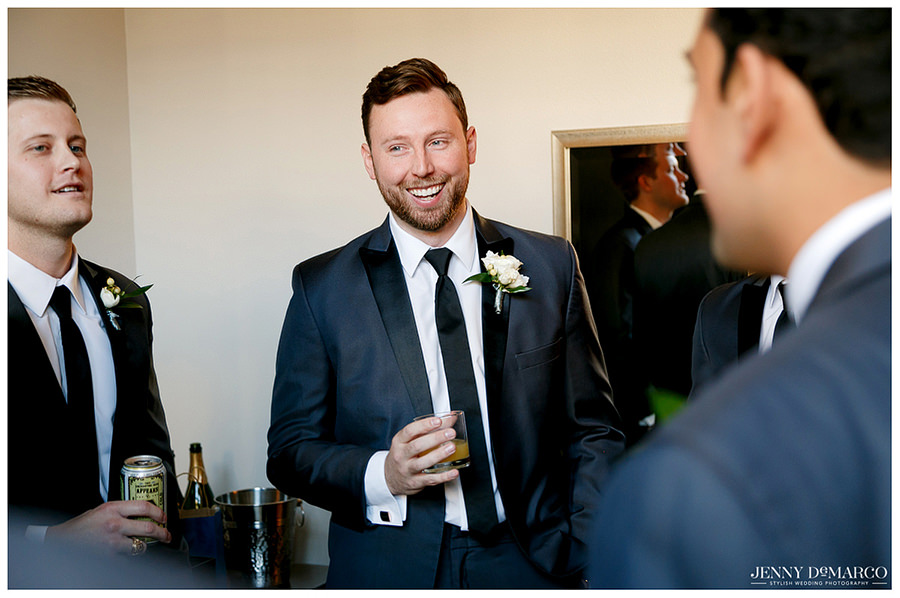 Groom smiling as his groomsmen give him a cheers