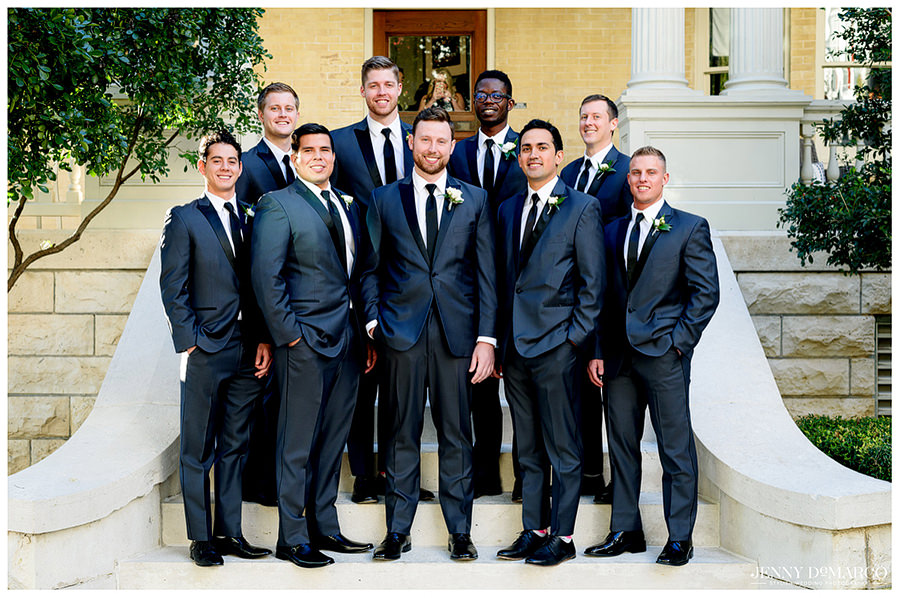 Groom and groomsmen posing in front of wedding venue